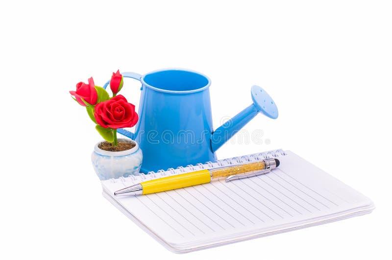 日志或笔记本、笔,红色玫瑰,玻璃和喷壶 库存照片