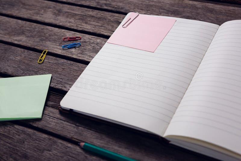 日志,稠粘的笔记,铅笔和纸夹在木桌上 免版税库存照片