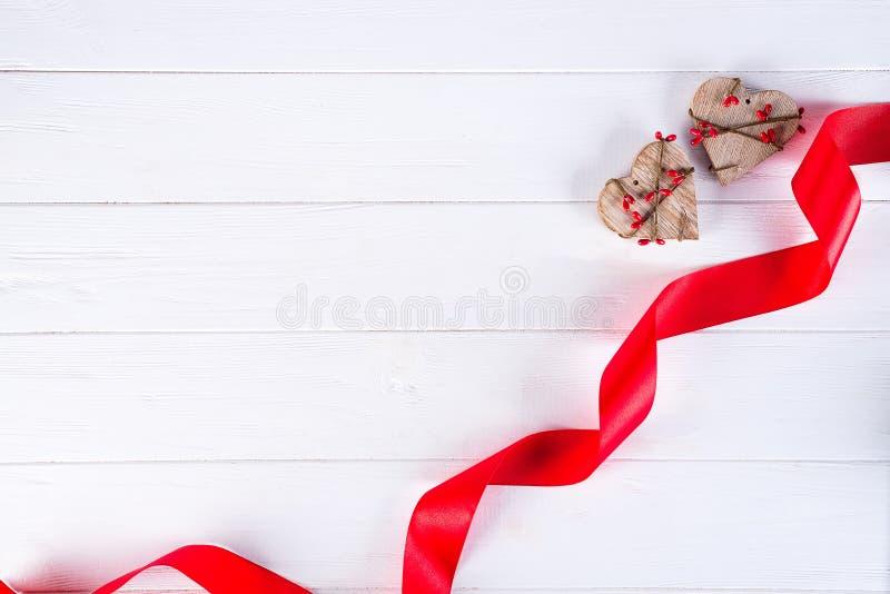 日愉快的华伦泰 红色丝带和两木心脏在白色背景 背景蓝色框概念概念性日礼品重点查出珠宝信函生活纤管红色仍然被塑造的华伦泰 库存图片