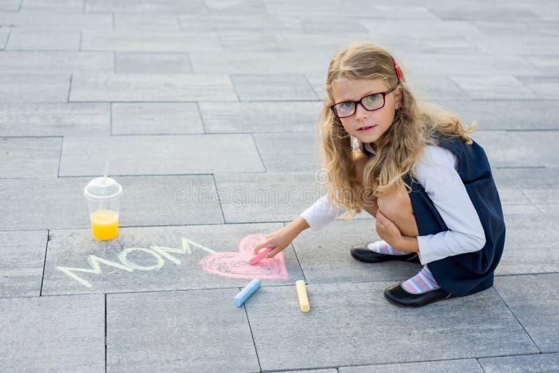 日愉快的母亲s 一个小女孩为她的母亲画蜡笔图片惊奇在沥青的 免版税库存图片