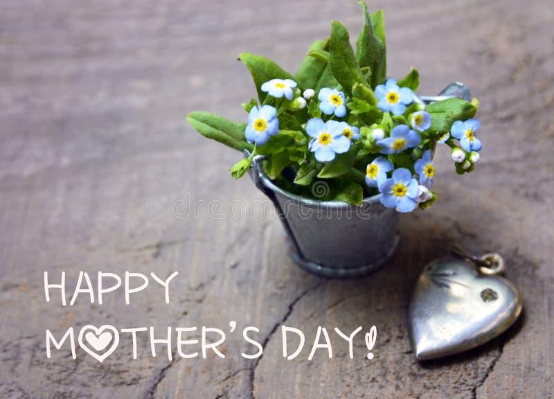 日愉快的母亲s 勿忘草在小金属桶和葡萄酒银色心脏开花在老木桌上 库存照片