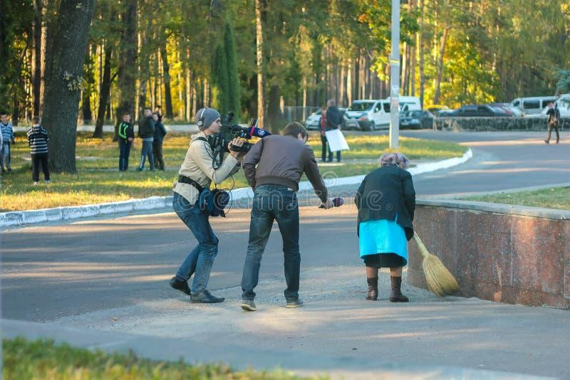 日托米尔,乌克兰- 2014年10月10日:从媒介的要求的人老妇人,当她清扫在街道上时的地板 免版税库存照片