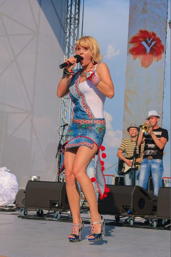 日托米尔,乌克兰- 2013年6月20日:唱歌白肤金发的歌手的女孩演奏在后院音乐会的活带与朋友 库存图片