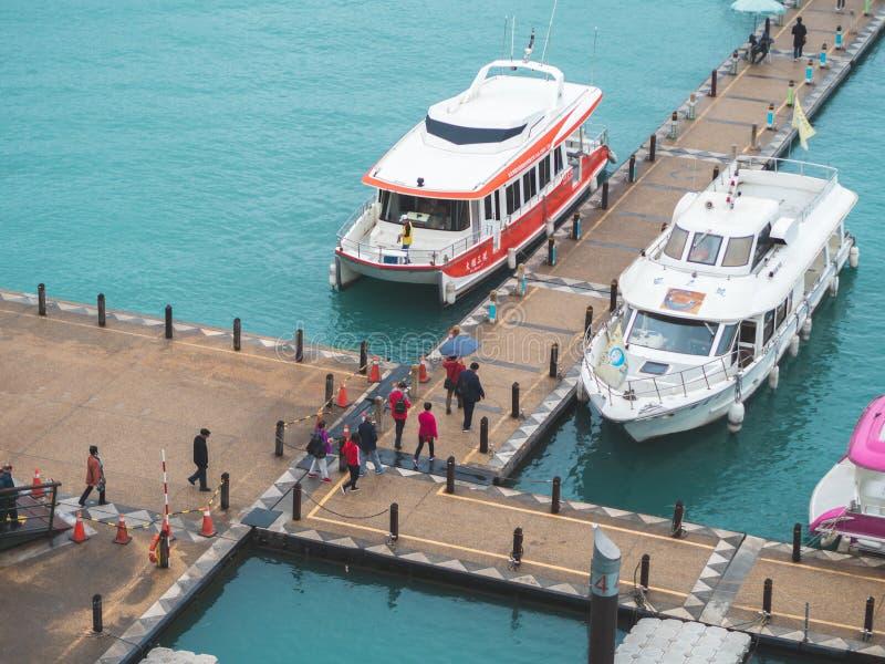 日月潭在码头的梭小船在有游人走到小船的一个小组的一个湖 免版税库存照片