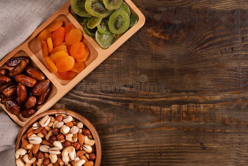 日期、杏干和猕猴桃在坚果的一个区划盘和分类在木碗在一张黑暗的木桌上 库存照片