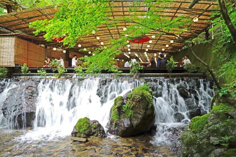 日本传统室外餐馆,禅宗庭院,瀑布,绿色植物 免版税库存照片