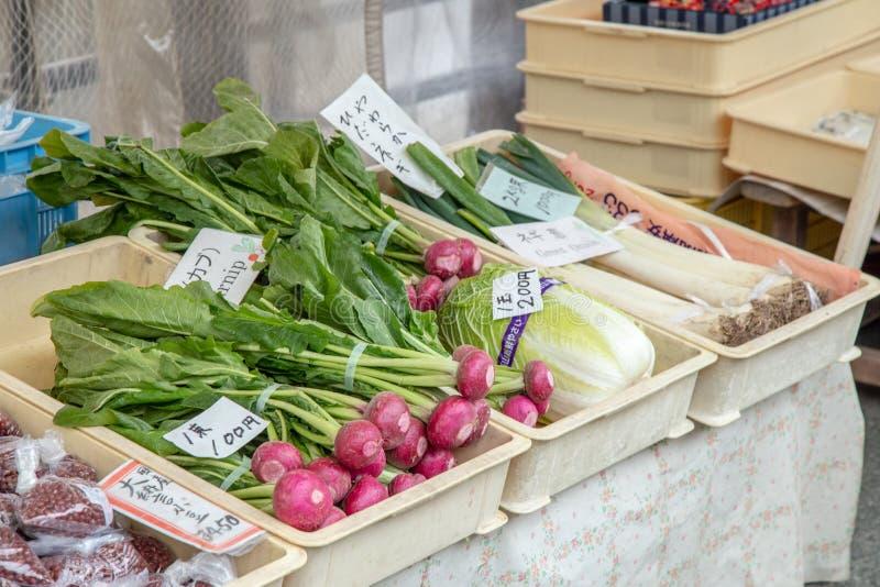 日本卖主卖新鲜蔬菜,纪念品,食物在地方Jinya Mae早晨市场上 免版税库存照片