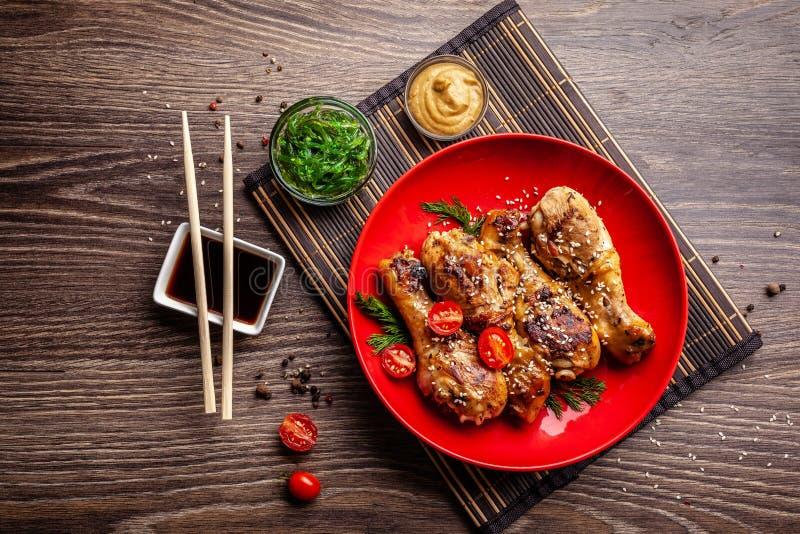 日本和中国烹调的概念 鸡油煎了有辣子的,芝麻,chuka沙拉,在木桌上的中国豌豆腿 免版税库存照片