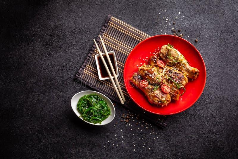 日本和中国烹调的概念 鸡油煎了有辣子的,芝麻,chuka沙拉,在黑桌上的中国豌豆腿 免版税库存图片