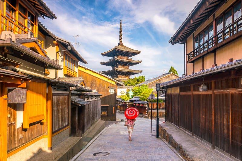 日本女孩在有红色伞的Yukata在老镇京都 免版税图库摄影