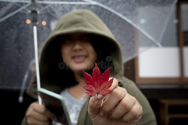 日本妇女佩带的敞篷毛线衣暴牙的微笑的面孔和红色 免版税库存图片