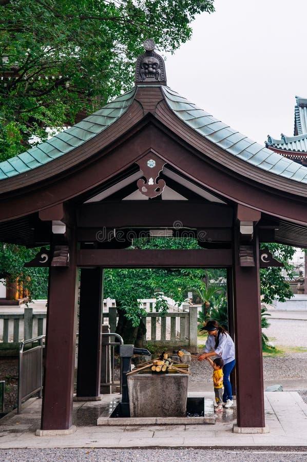 日本家庭在Temizuya圣水亭子洗他们的手 库存照片