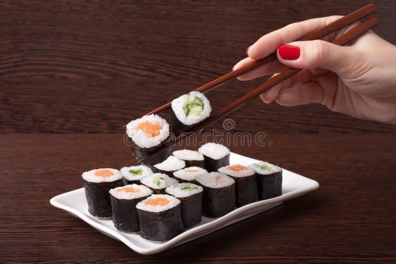 日本寿司传统日本料理,有筷子的手 免版税图库摄影