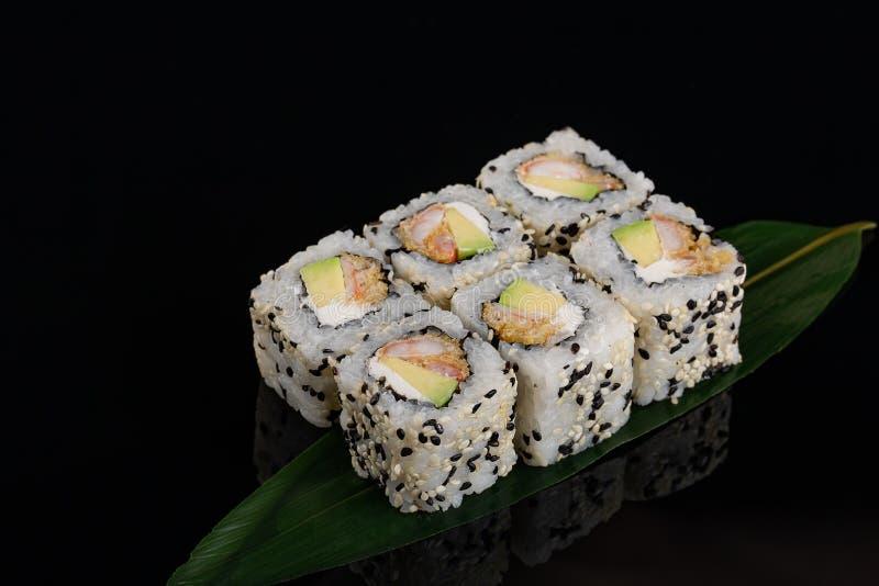 日本寿司虾天麸罗卷特写镜头视图在香蕉叶子的在黑背景 图库摄影