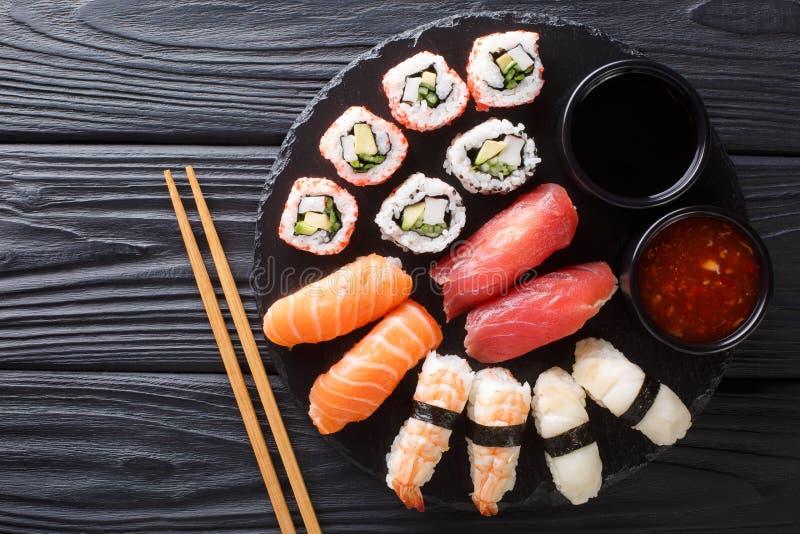 日本寿司食物 梅基ands滚动与金枪鱼、三文鱼、虾、螃蟹和鲕梨与两个调味汁特写镜头在板岩 水平 库存照片