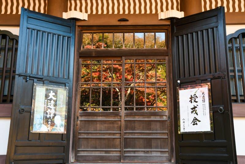 日本庙的玻璃门上映着秋叶 免版税库存图片