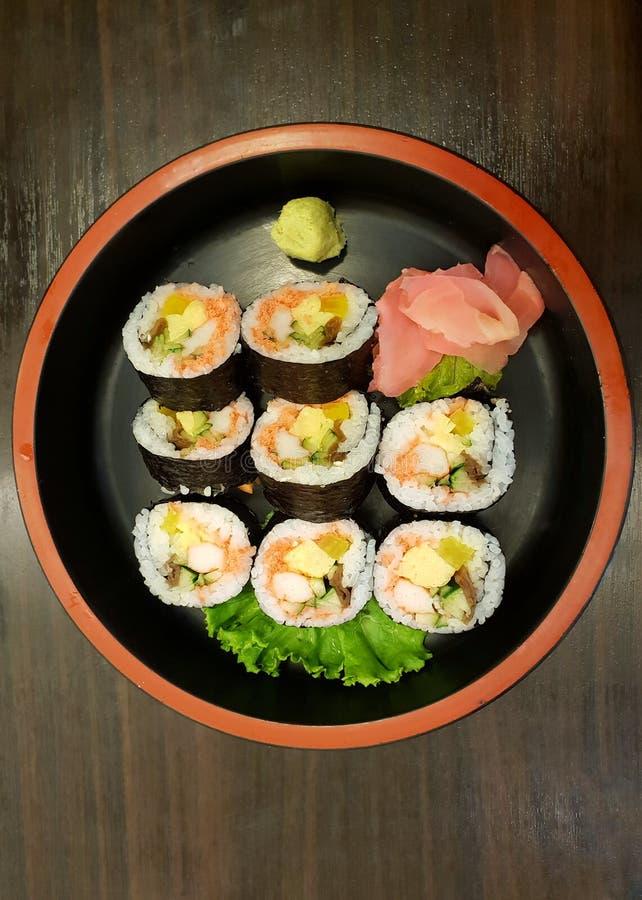 日本料理样式,寿司卷顶视图冠上与三文鱼,菜,gari和山葵 免版税图库摄影