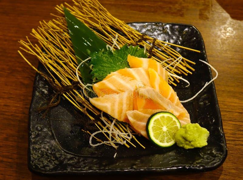 日本料理生鱼片三文鱼在黑色的盘子 免版税库存图片