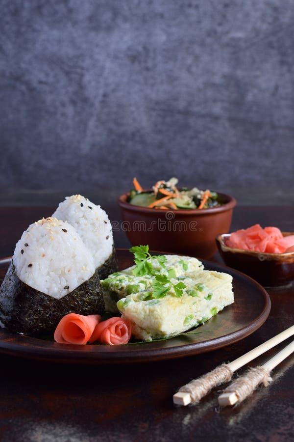 日本料理-米饭团onigiri、煎蛋卷、烂醉如泥的姜、sunomono wakame黄瓜沙拉和筷子的混合 ?? 免版税库存图片