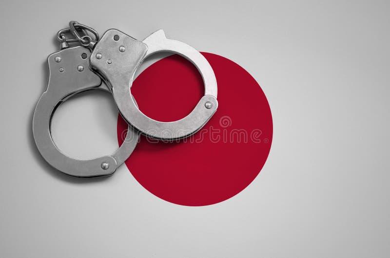 日本旗子和警察手铐 罪行和进攻的概念在国家 免版税库存图片