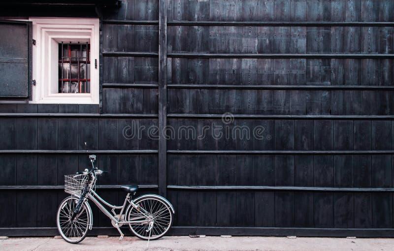 日本有老hou黑木墙壁的葡萄酒白色自行车  库存照片