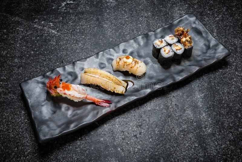 日本海鲜寿司、卷和筷子在一个黑色的盘子 免版税库存图片