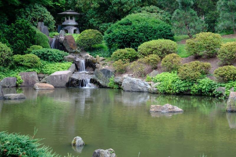 日本石灯笼和瀑布到Koi鱼池里在 免版税图库摄影