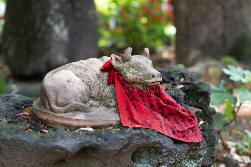 日本神社中的宁静奶牛雕像 免版税库存照片