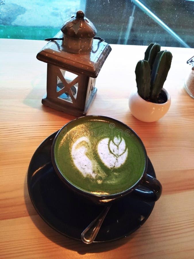 日本绿色matcha拿铁茶牛奶艺术黑杯子灯笼仙人掌照片 库存图片
