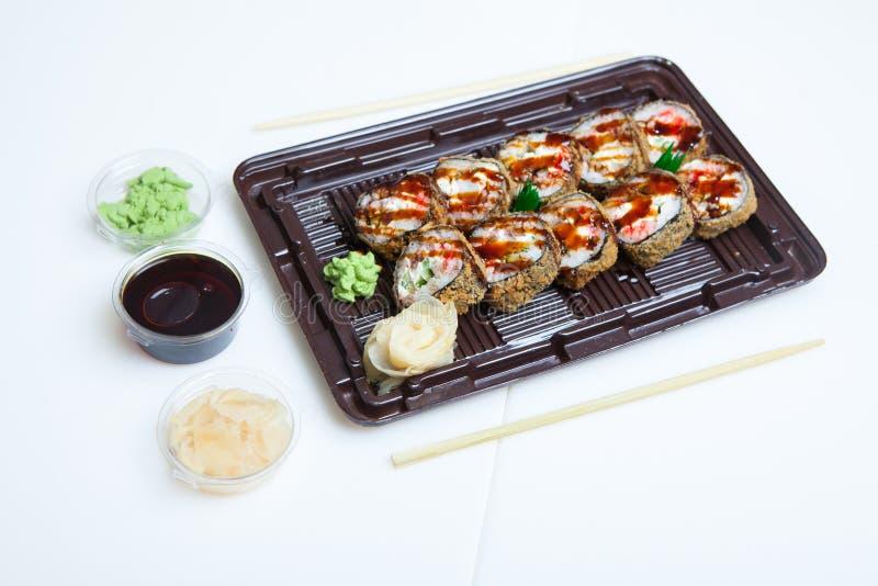 日本食物在塑料盒滚动 在白色背景在塑料包裹关闭的寿司集合隔绝的 寿司为拿走或 免版税库存照片