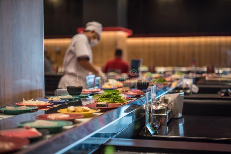 日本食物餐馆传送带自助餐和厨师 免版税图库摄影