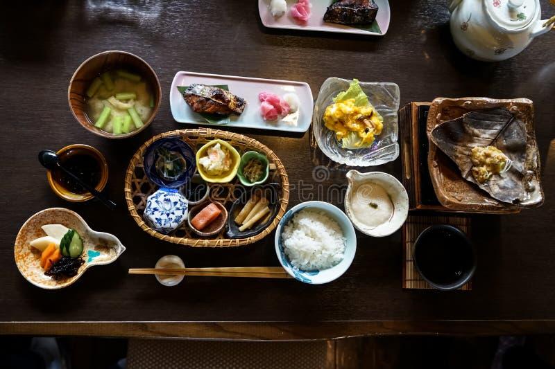 日本ryokan早餐盘包括煮熟的白米,烤鱼,煎蛋,汤, mentaiko,腌汁,海草,热板 免版税图库摄影
