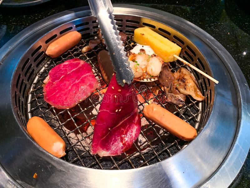 日本Yakiniku烤肉格栅用肉、香肠、扇贝和蛋卷 库存图片