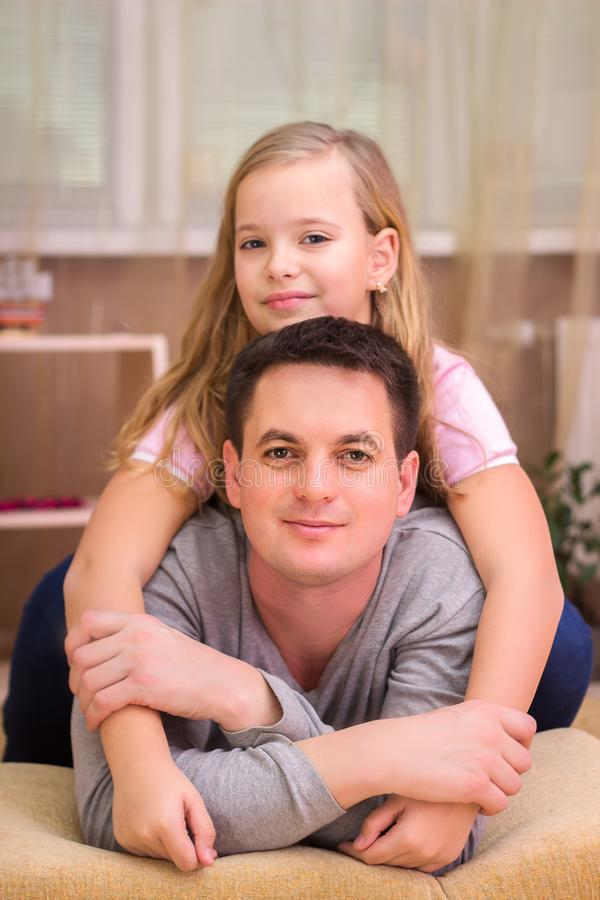 日父亲s 拥抱爸爸和笑在的愉快的家庭女儿ho 免版税图库摄影
