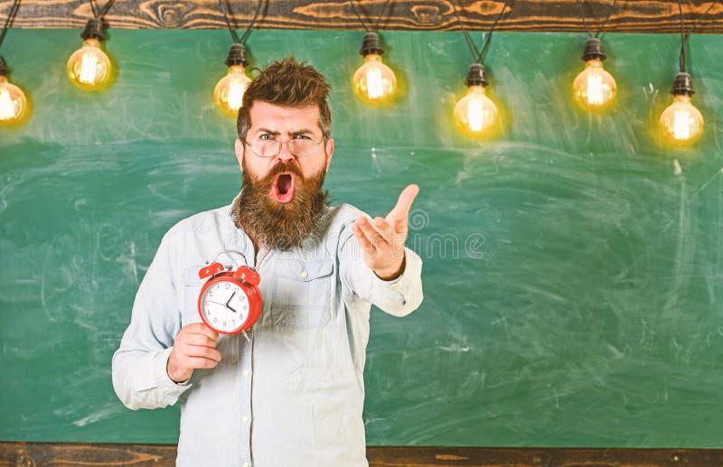 日程表和政权概念 镜片的老师拿着闹钟 有胡子的人在争论的呼喊的面孔 库存图片