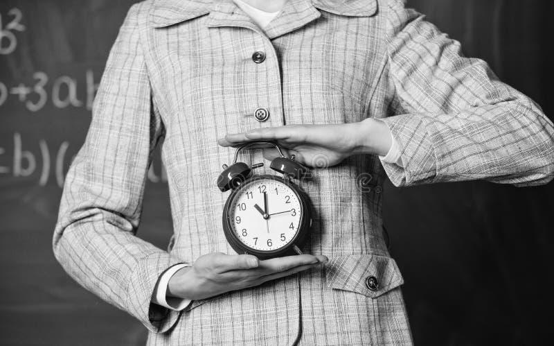 日程表和政权 闹钟在紧密女性手上 老师属性 闹钟在老师的手上或 免版税库存照片