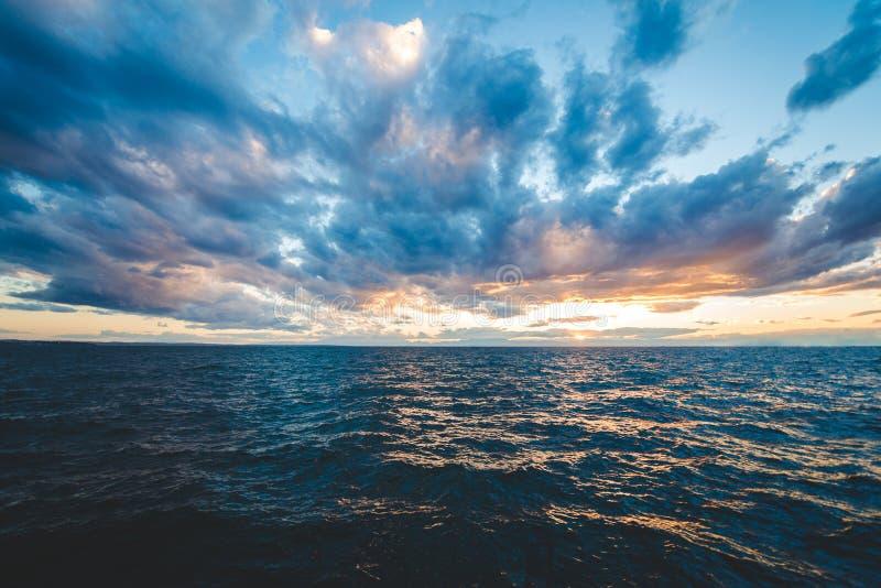 日落与剧烈的天空和五颜六色的云彩的海视图 免版税库存照片