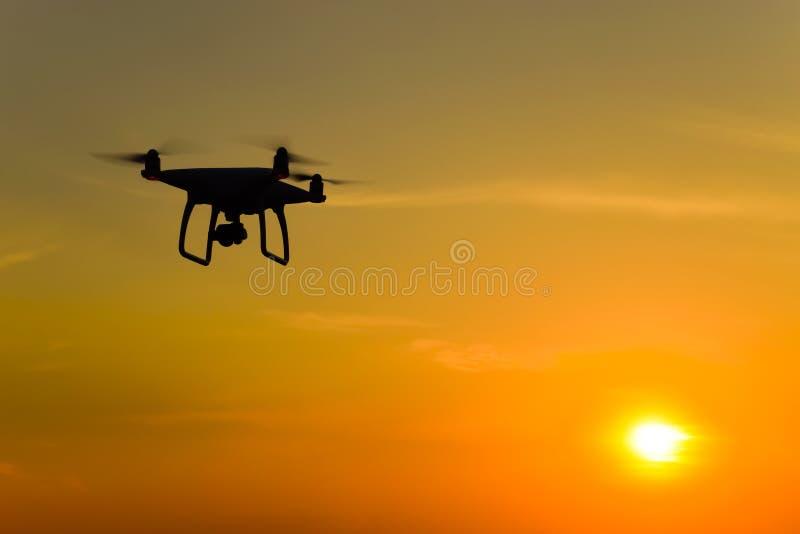 以日落为背景的Quadrocopters剪影 在晚上天空的飞行寄生虫 免版税库存照片