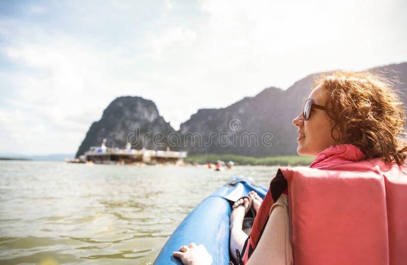 日落乘驾的少妇旅客在皮船-绊倒旅行概念 图库摄影
