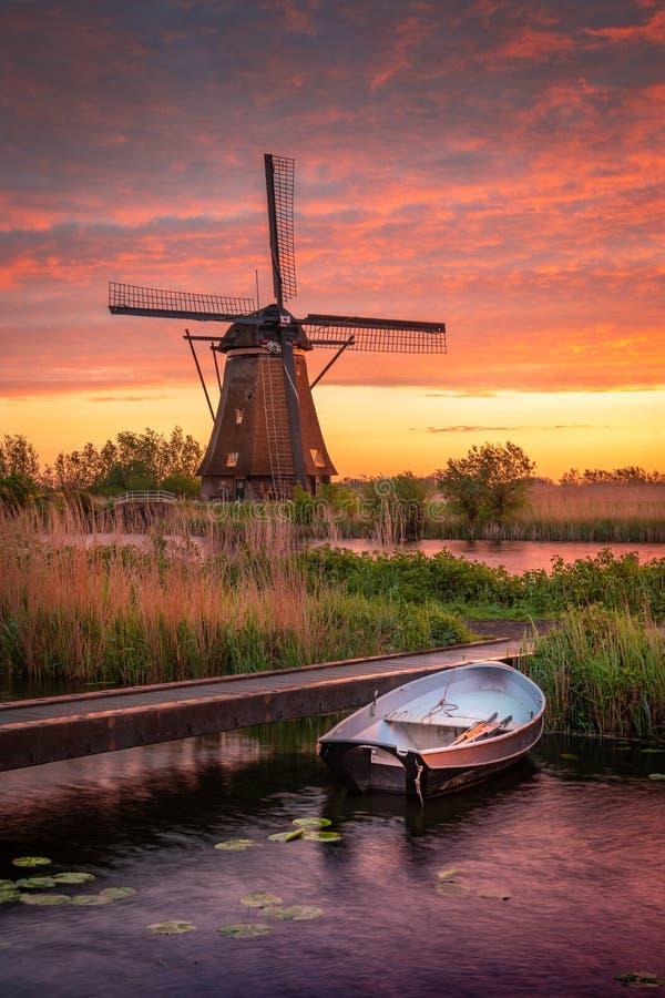 日落云霄下湖中小船和背景磨坊的垂直照片 免版税库存图片