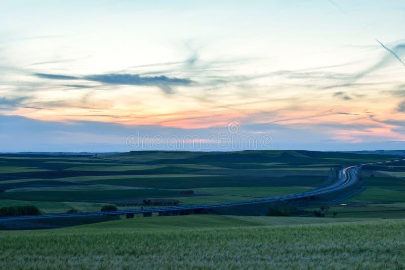 日落五颜六色的风景在农田里 免版税库存图片
