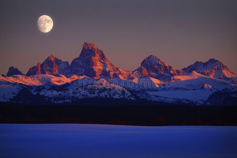 日落光在Tetons Teton山的阿尔彭焕发与月亮上升 图库摄影