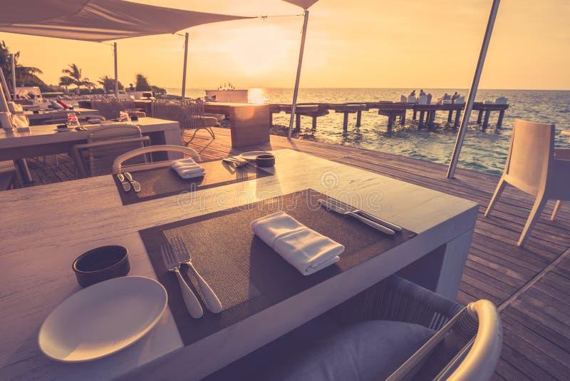 日落光的喜怒无常的海滩胜地餐馆 最低纲领派桌设定 免版税库存图片