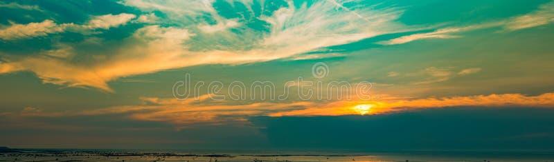 日落全景视图在海滩的 美丽的蓝色和橙色天空和云彩与阳光 E ?? 库存照片