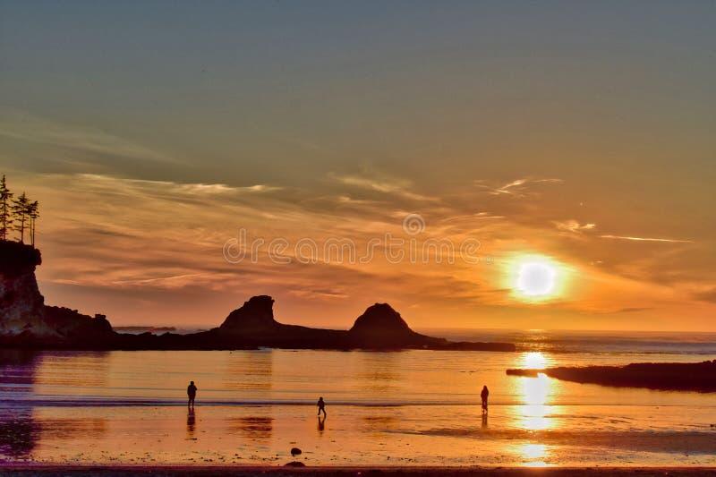 日落和剪影在俄勒冈海滩 库存照片