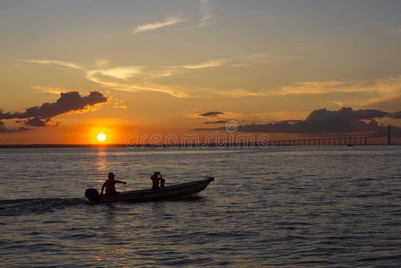 日落和剪影在巡航的小船亚马孙河,巴西 免版税库存照片
