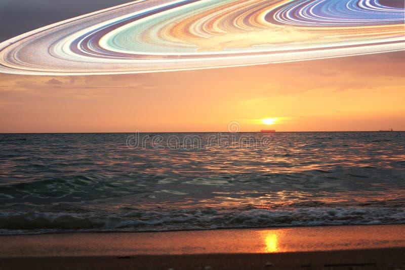 日落和土星环五颜六色水平的海水的表面上 免版税库存照片