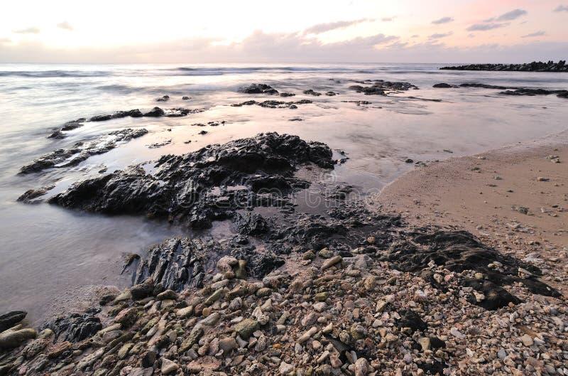 日落和多岩石的海滩 免版税库存照片