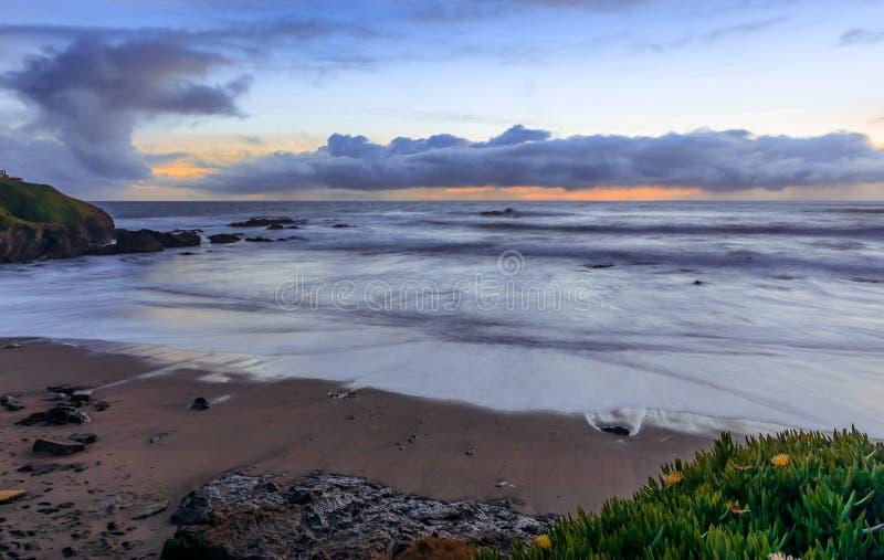 日落和柔滑的水的淡色从碰撞由鸽子点灯塔的波浪长的曝光在加利福尼亚北部 图库摄影