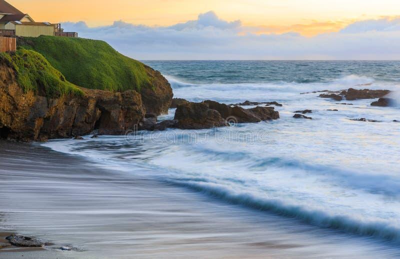 日落和柔滑的水的淡色从碰撞由鸽子点灯塔的波浪长的曝光在加利福尼亚北部 免版税图库摄影